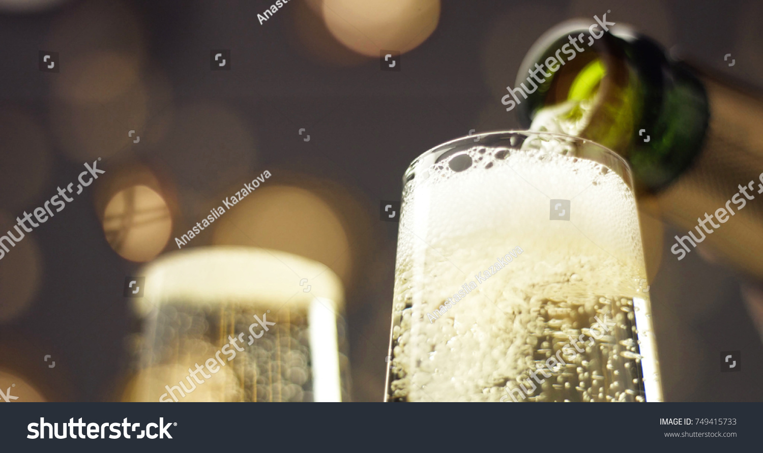 Bottle of sparkling wine with three flute glasses with bubbles floating up on gray backgrounds with Christmas lights #749415733