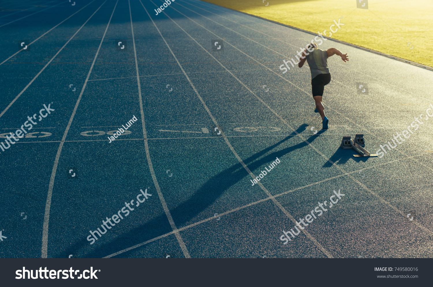 Athlete running on an all-weather running track alone. Runner sprinting on a blue rubberized running track starting off using a starting block. #749580016