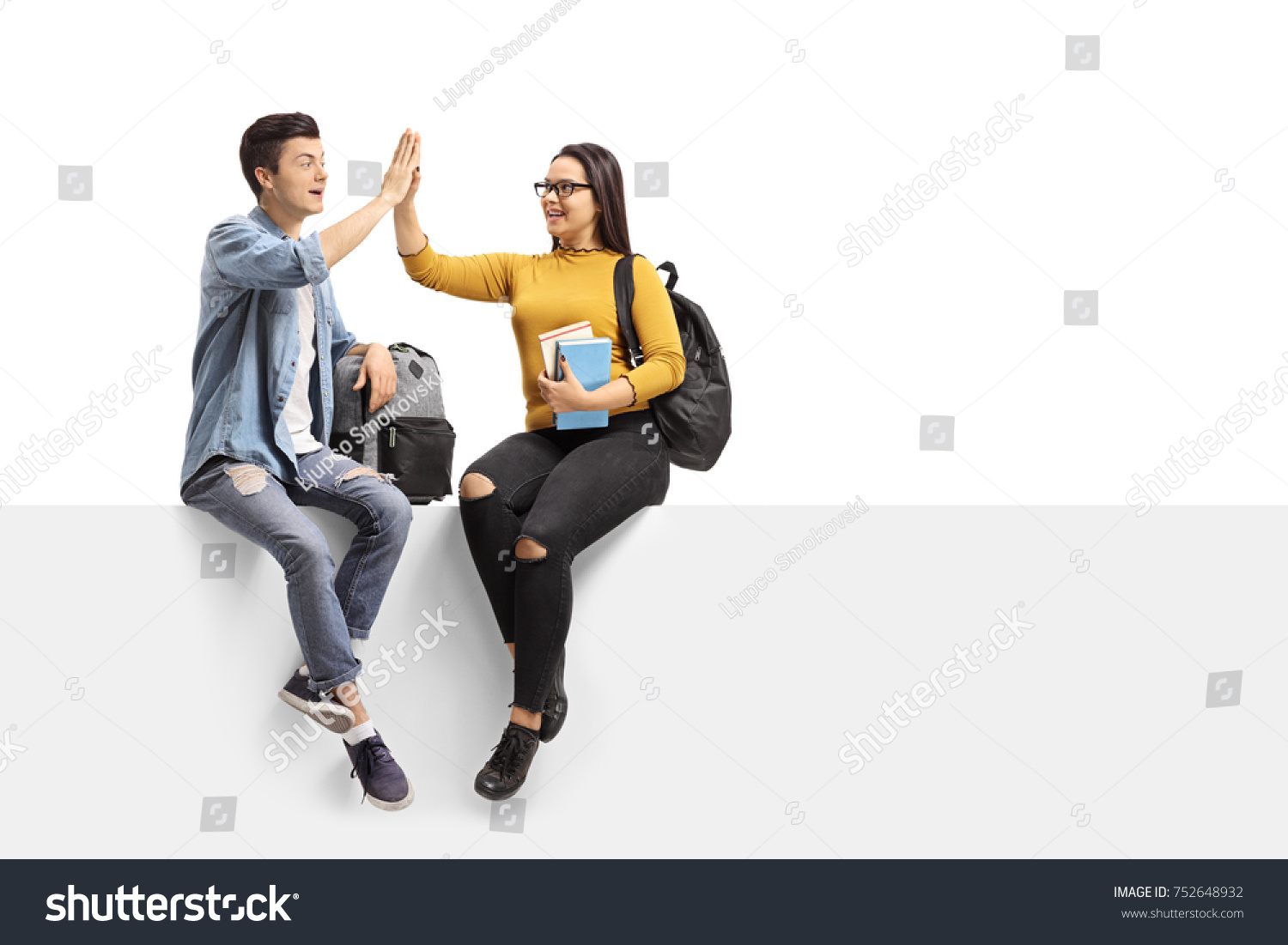 Teenage students sitting on a panel and high-fiving each other isolated on white background