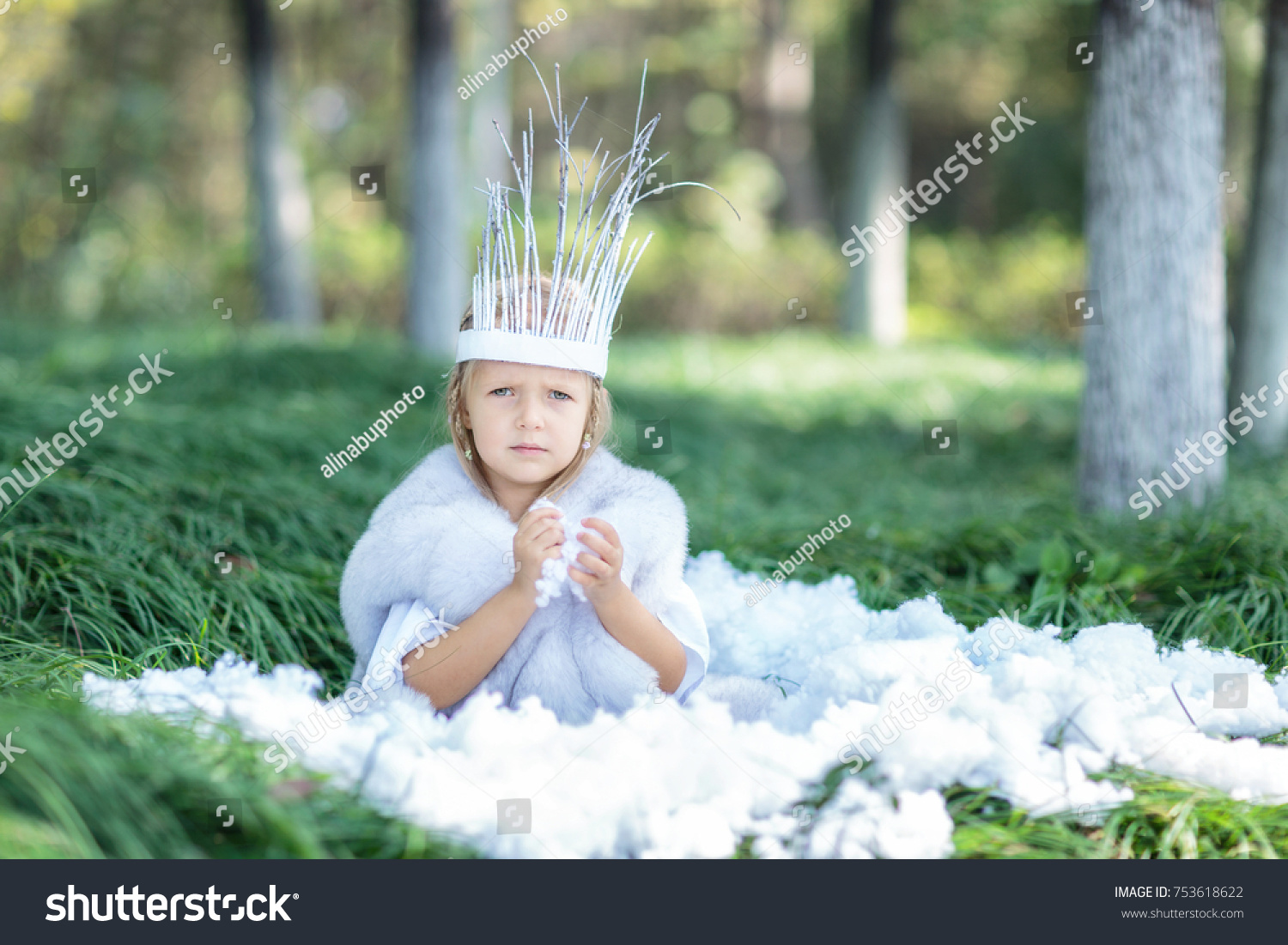 Portrait of a beautiful little girl in a snow queen costume with a crown on her