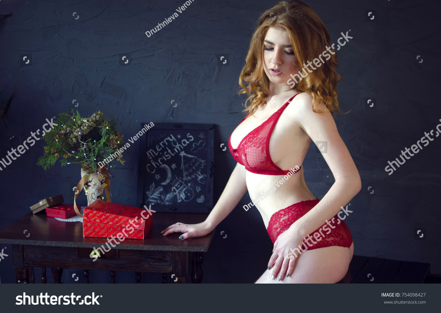 ba481a33100 Young redhead beautiful woman in red lace lingerie on the black wall  background