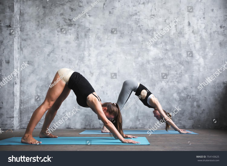 Two Young Beautiful Women Doing Yoga Asana Couple Pose