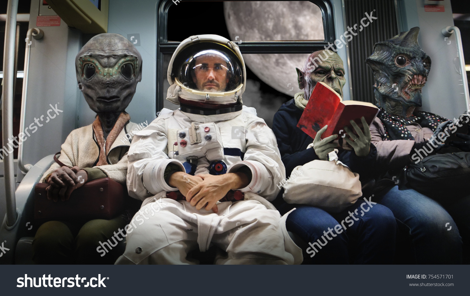 On a spaceship, an astronaut, sitting alongside extraterrestrial monsters, travel in total relaxation reading a book. Concept of space transport, surrealism, future, new worlds. #754571701