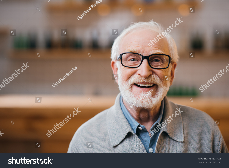 close-up portrait of happy senior man looking at camera #754621423
