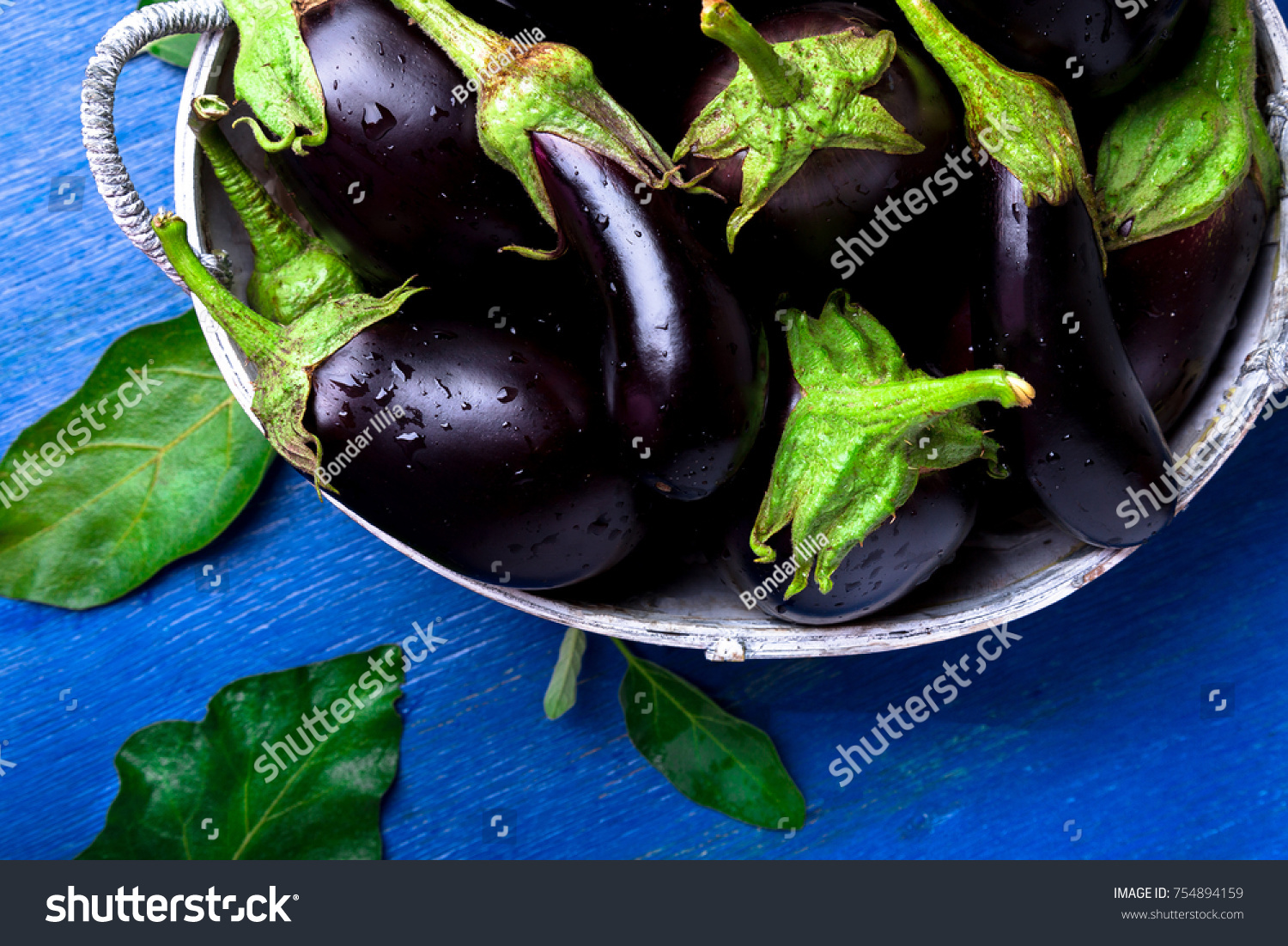 Fresh Eggplant In Grey Basket On Blue Wooden Table.Rustic Background. Top  View.