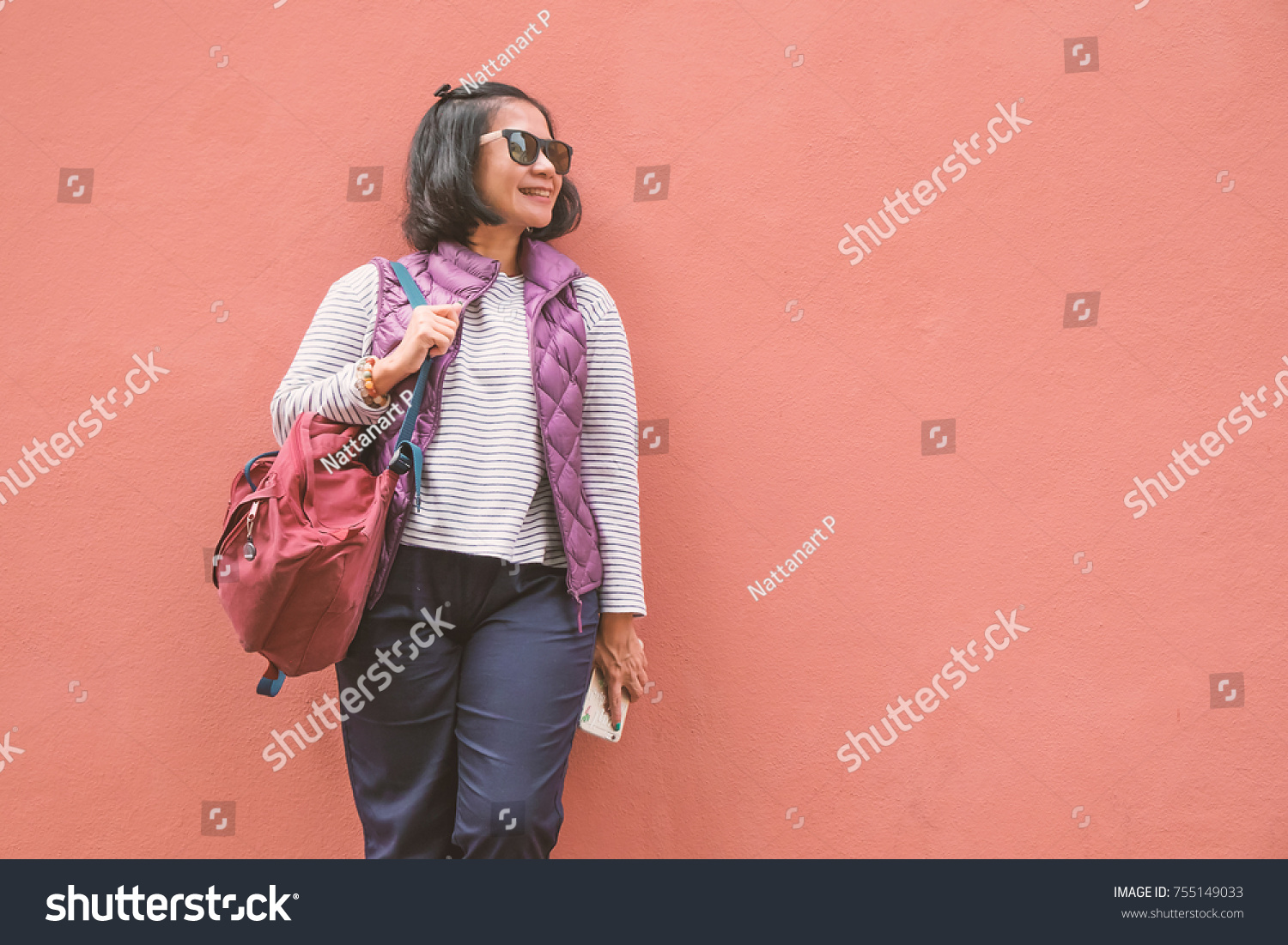 9f89cb568d10 Upper body portrait of an Asian woman carrying backpack and leaning on  orange concrete wall smiling