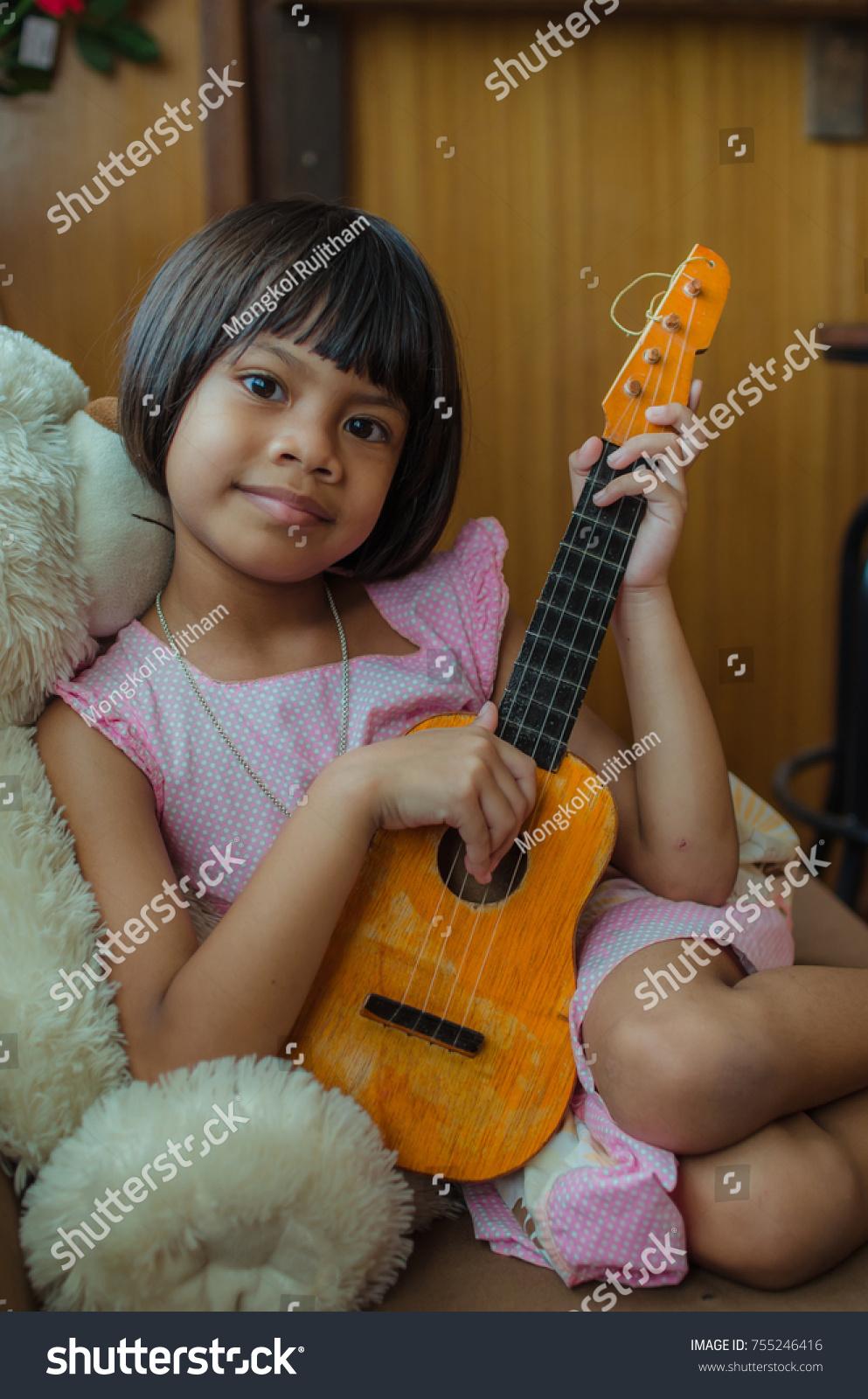 Asian Child Happy Play Ukulele In Bedroom