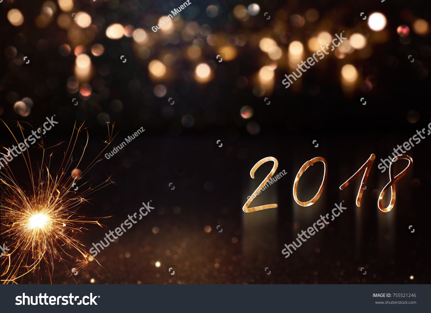 new year greetings 2018 with festive golden bokeh and sparkler