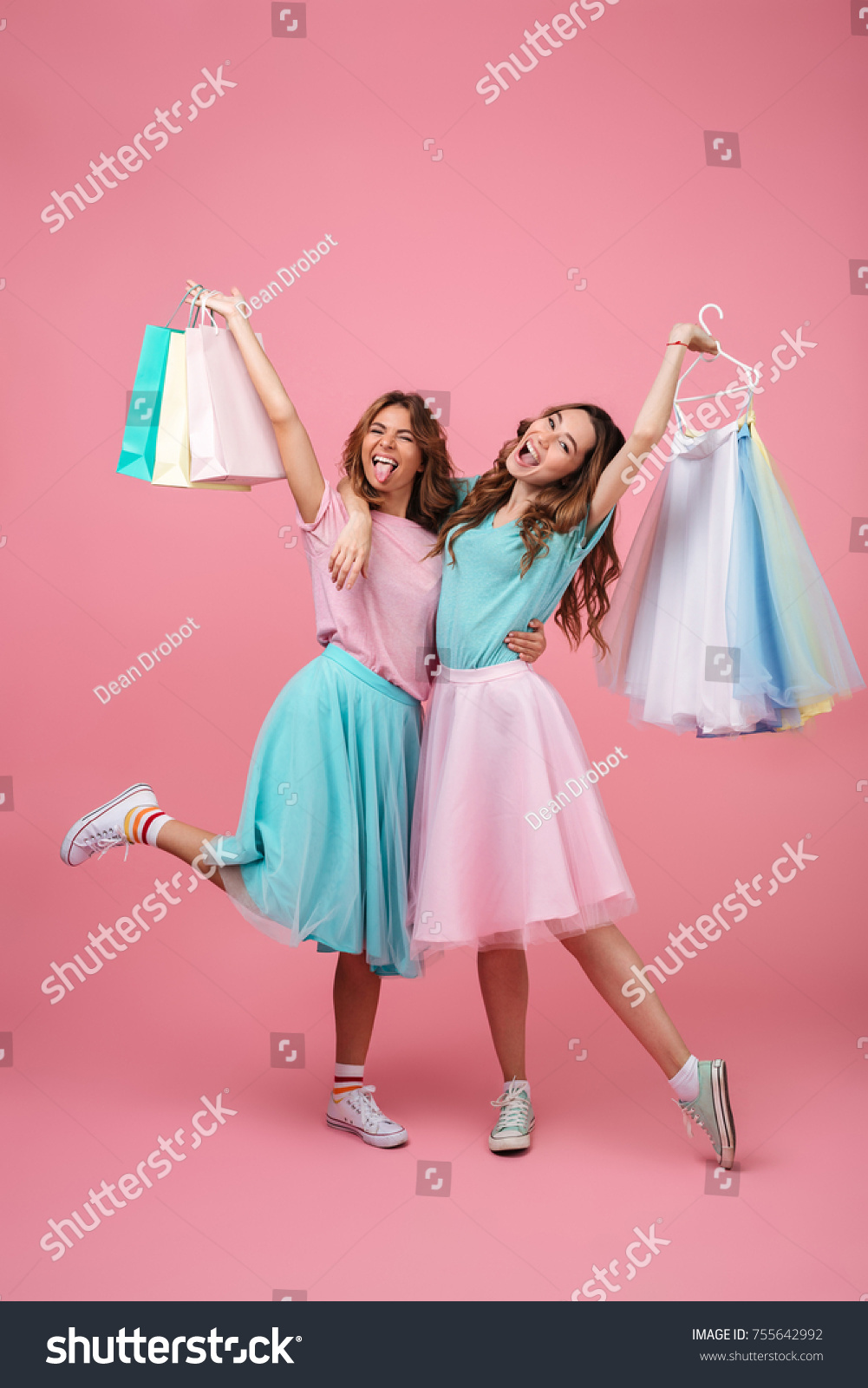 Full length portrait of two cheerful young girls dressed in bright colorful clothes holding shopping bags isolated over pink background #755642992