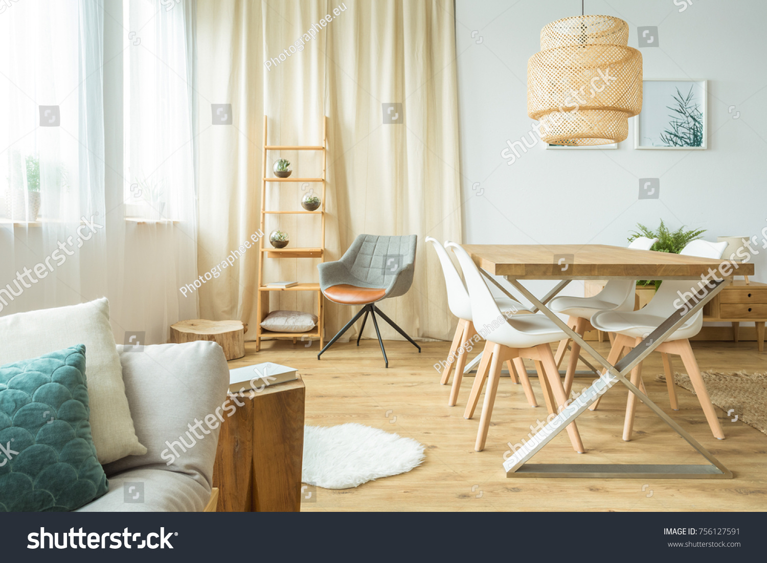 Rattan Lamp Above Table And Chairs In Multifunctional Dining Room With Sofa  And Poster On The
