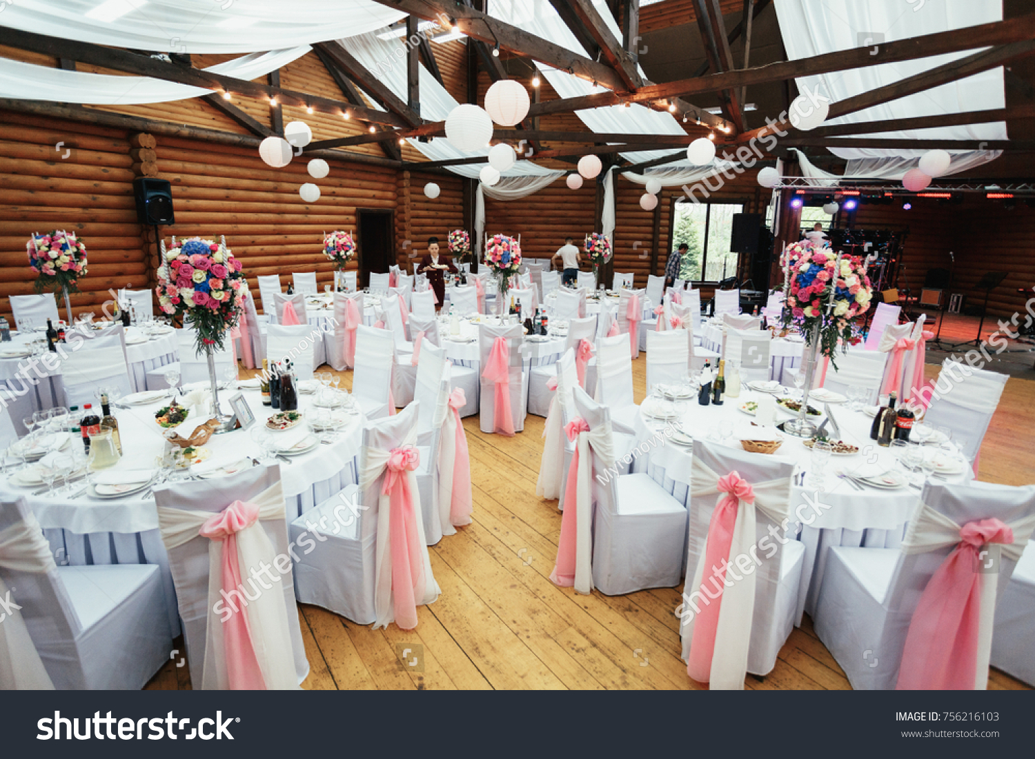 White Chairs Decorated With Pink Bows Stand At Round Tables In Wooden  Restaurant Hall