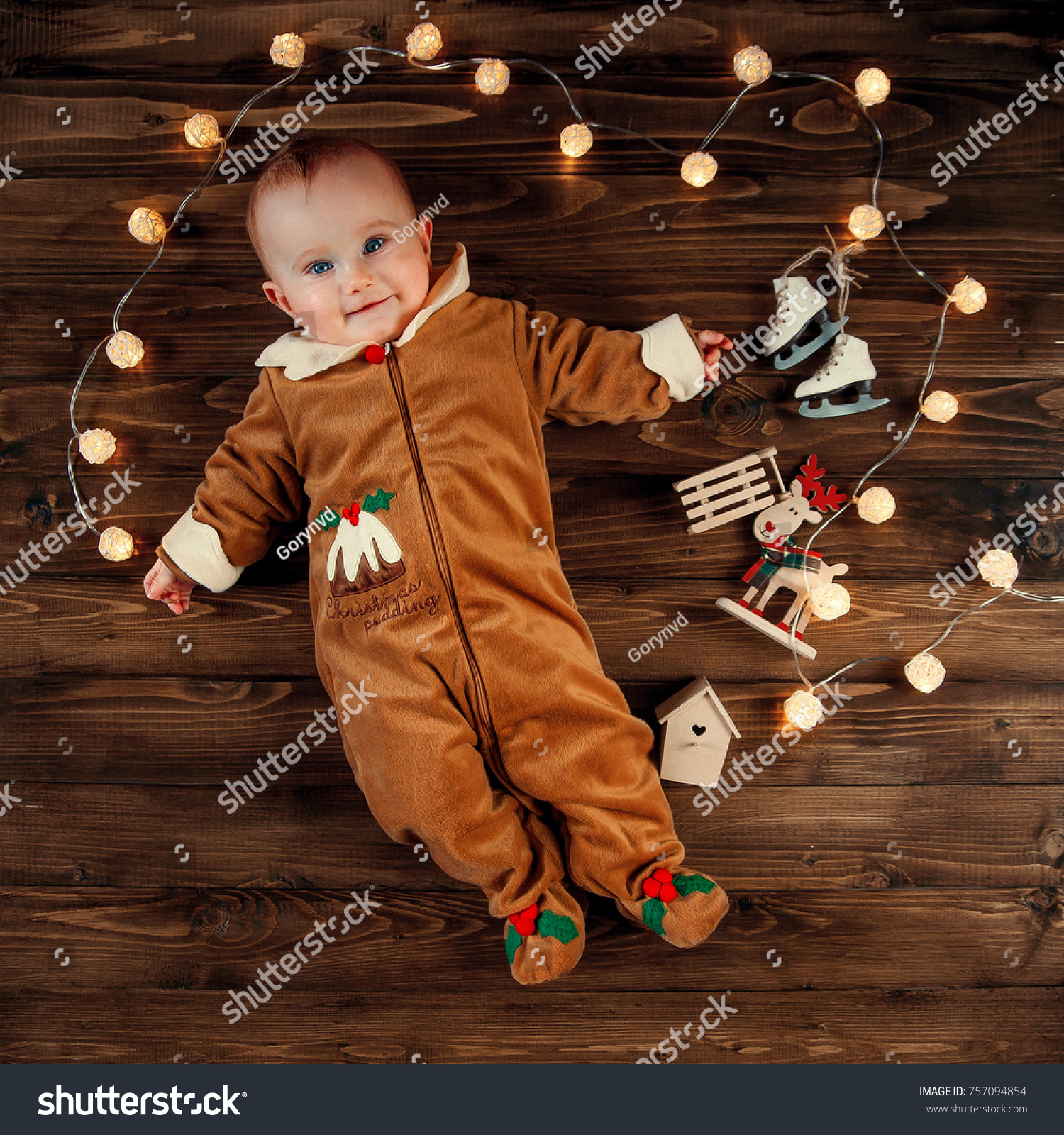 8dbf3c5cbf377 Cheerful cute baby in festive clothes is lying with Christmas lights and  decorations on a wooden