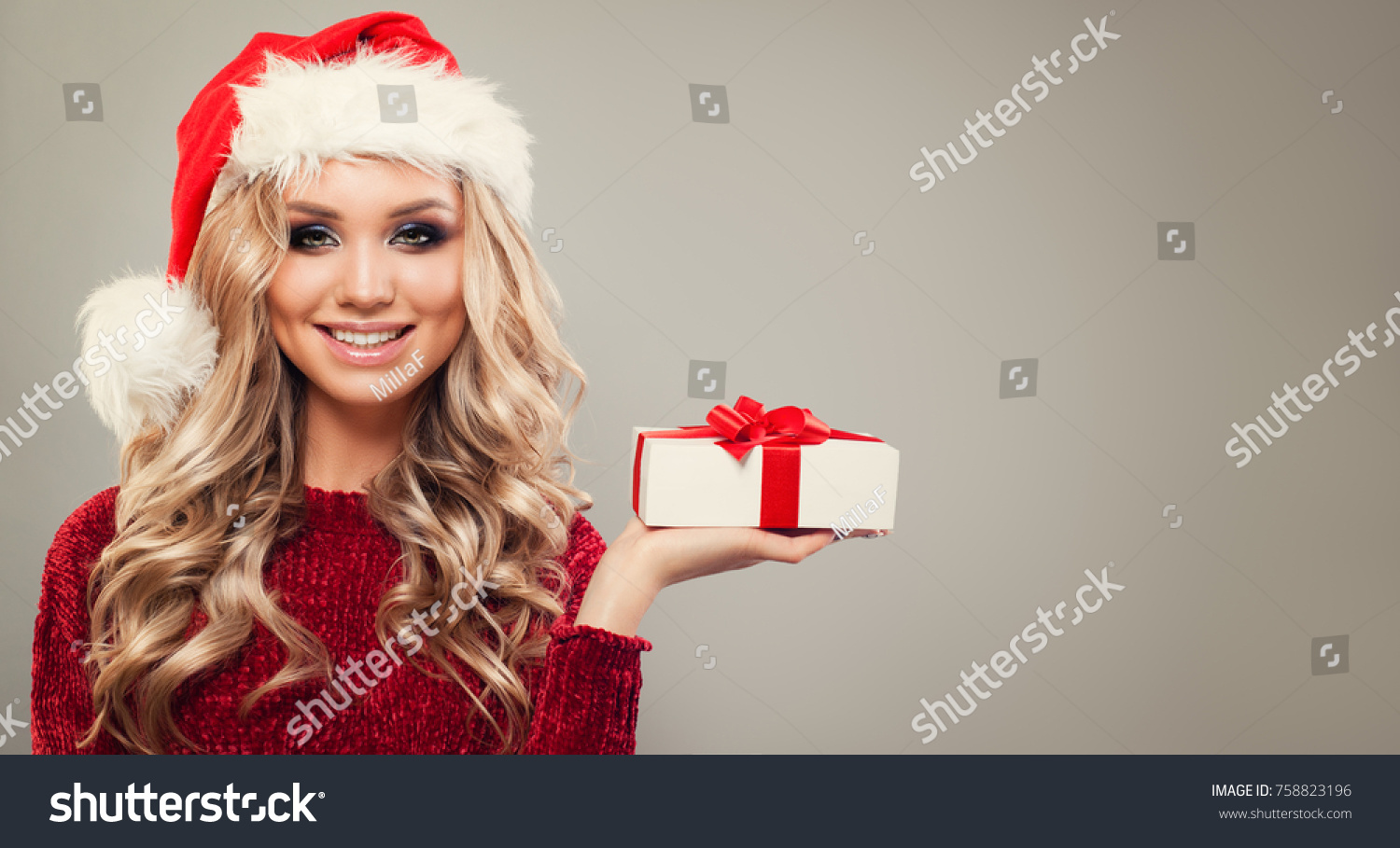 aaf3f4aa7a5e7 Christmas Woman in Santa Hat holding Gift. Happy Model with Brown Hair and Christmas  Gift