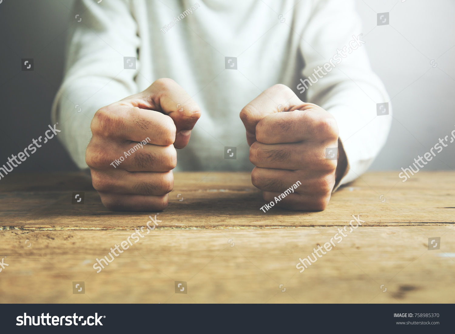 man fists clenched on a wooden table in anger #758985370
