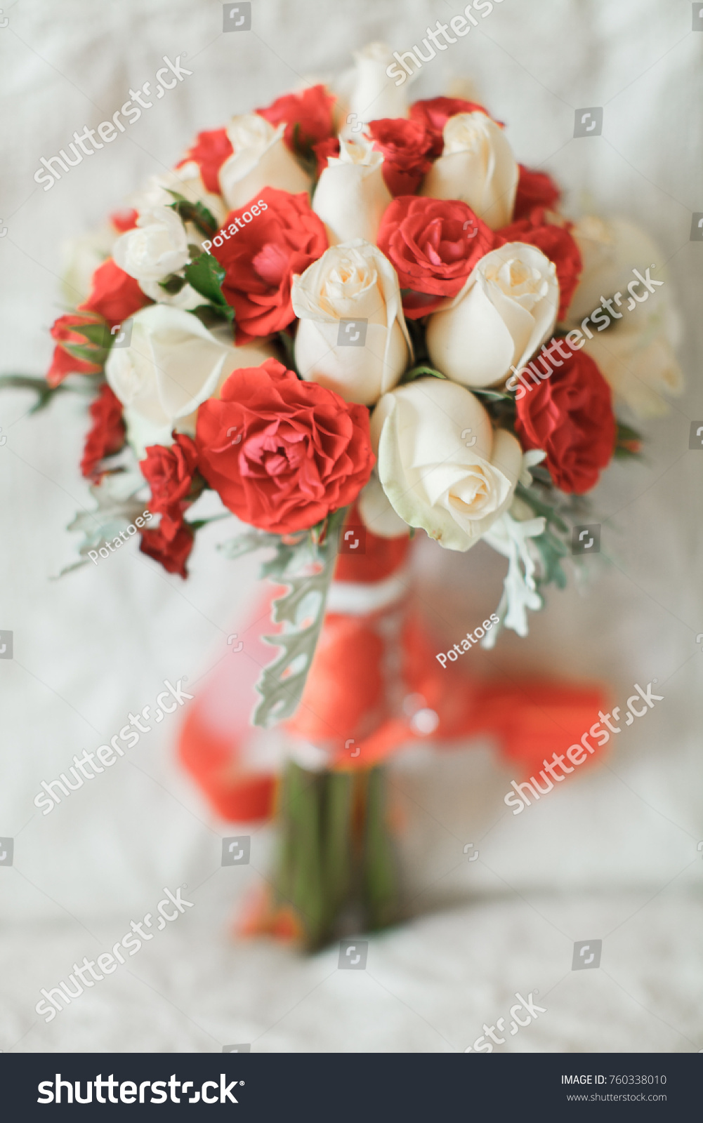 Wedding Bouquet Of Red And White Rose And Ribbon With Wedding Rings