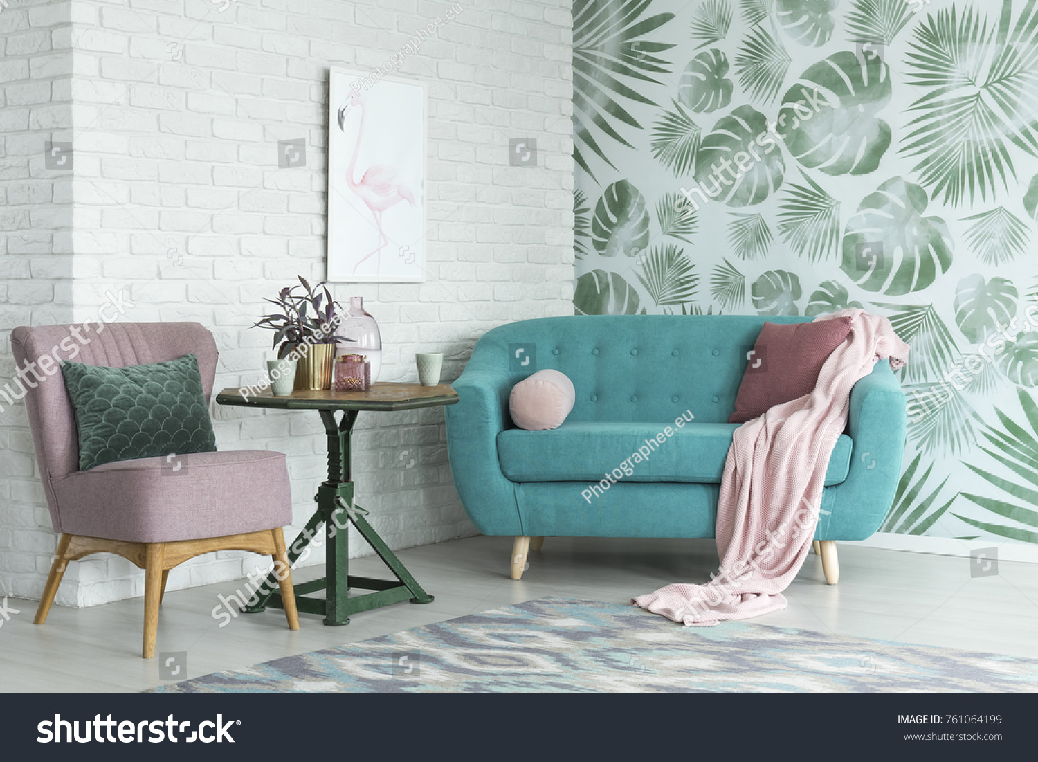 Green table with a plant between pink chair and blue sofa in floral living room with wallpaper and poster #761064199