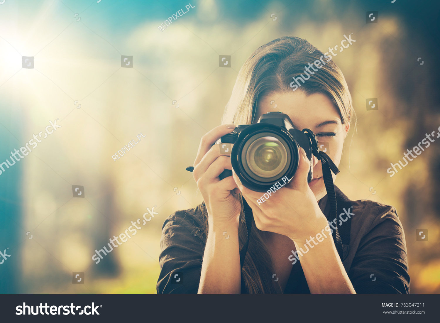 Portrait of a photographer covering her face with the camera. #763047211
