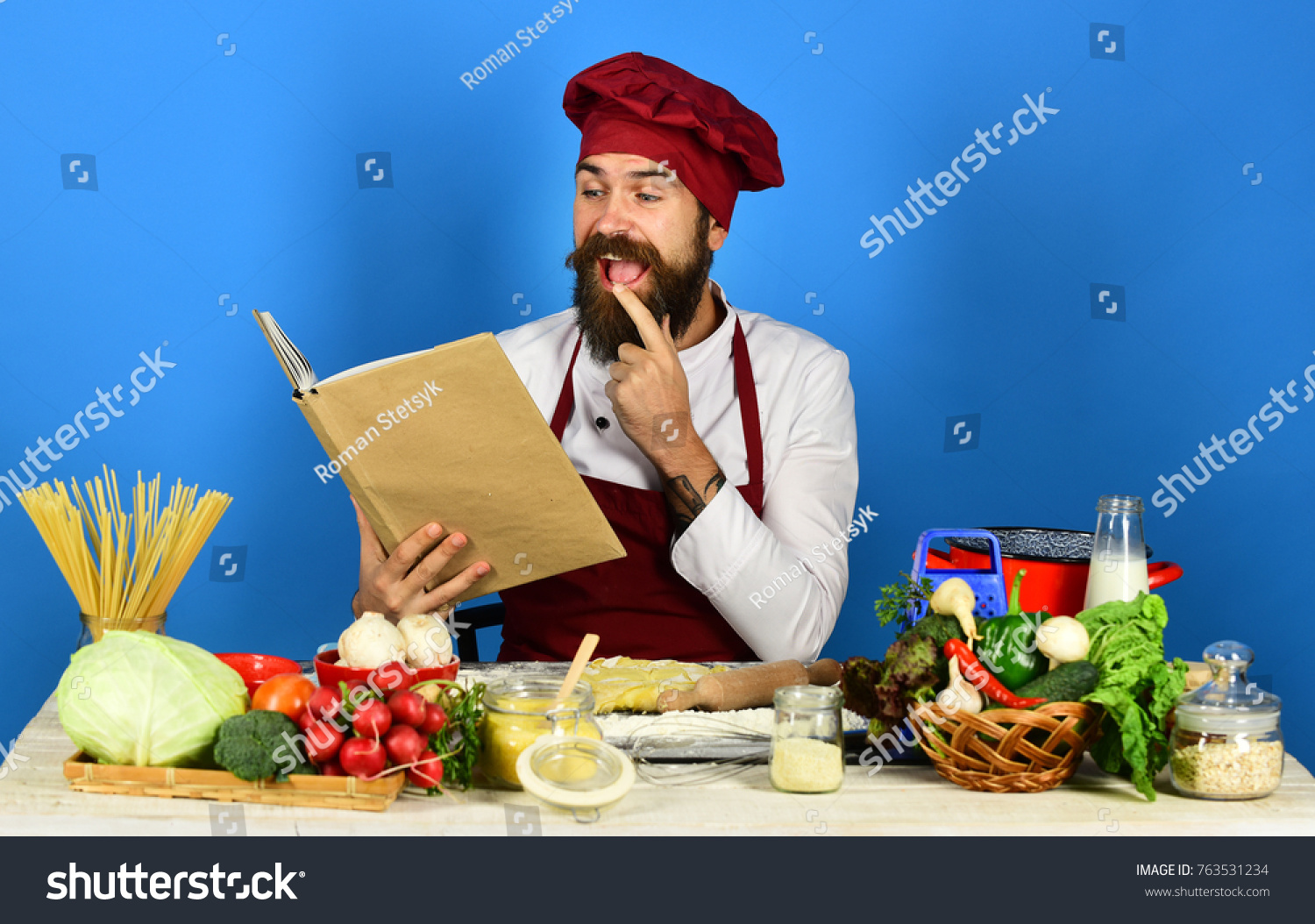 Man beard holds recipe book menu stock photo royalty free man with beard holds recipe book or menu on blue background chef near pasta forumfinder Image collections