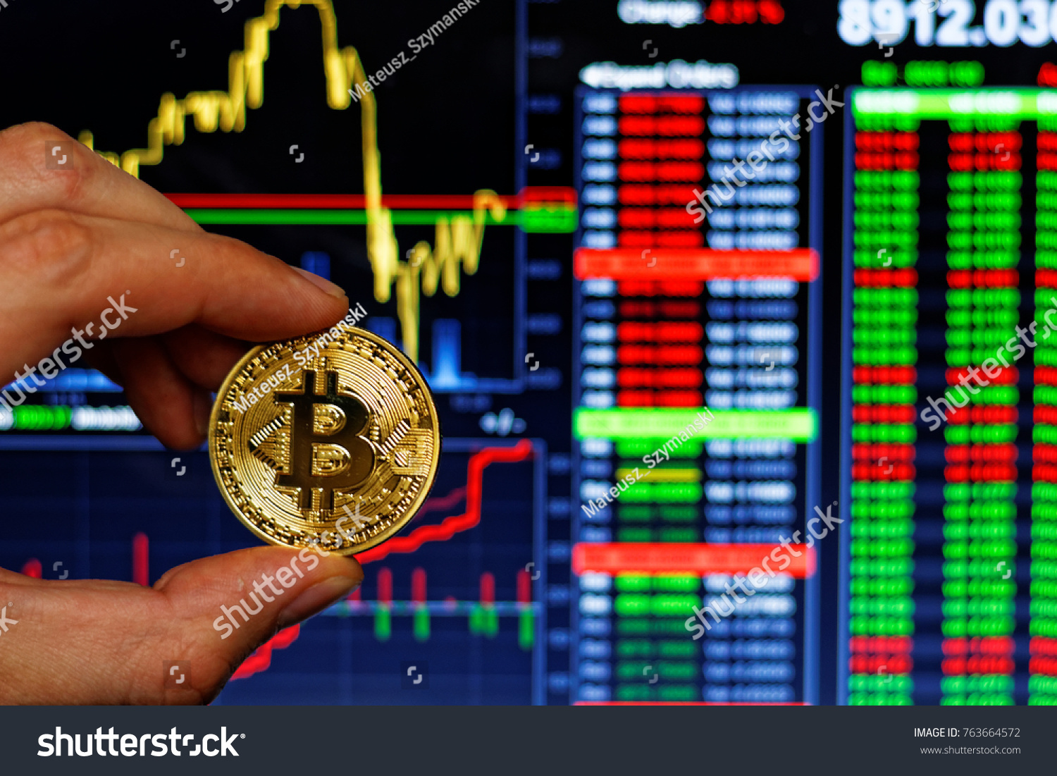 Mans hand holding gold bitcoin on stock photo 763664572 shutterstock mans hand holding gold bitcoin on stock market chart bitcoin symbol of investment in cryptocurrency biocorpaavc Images