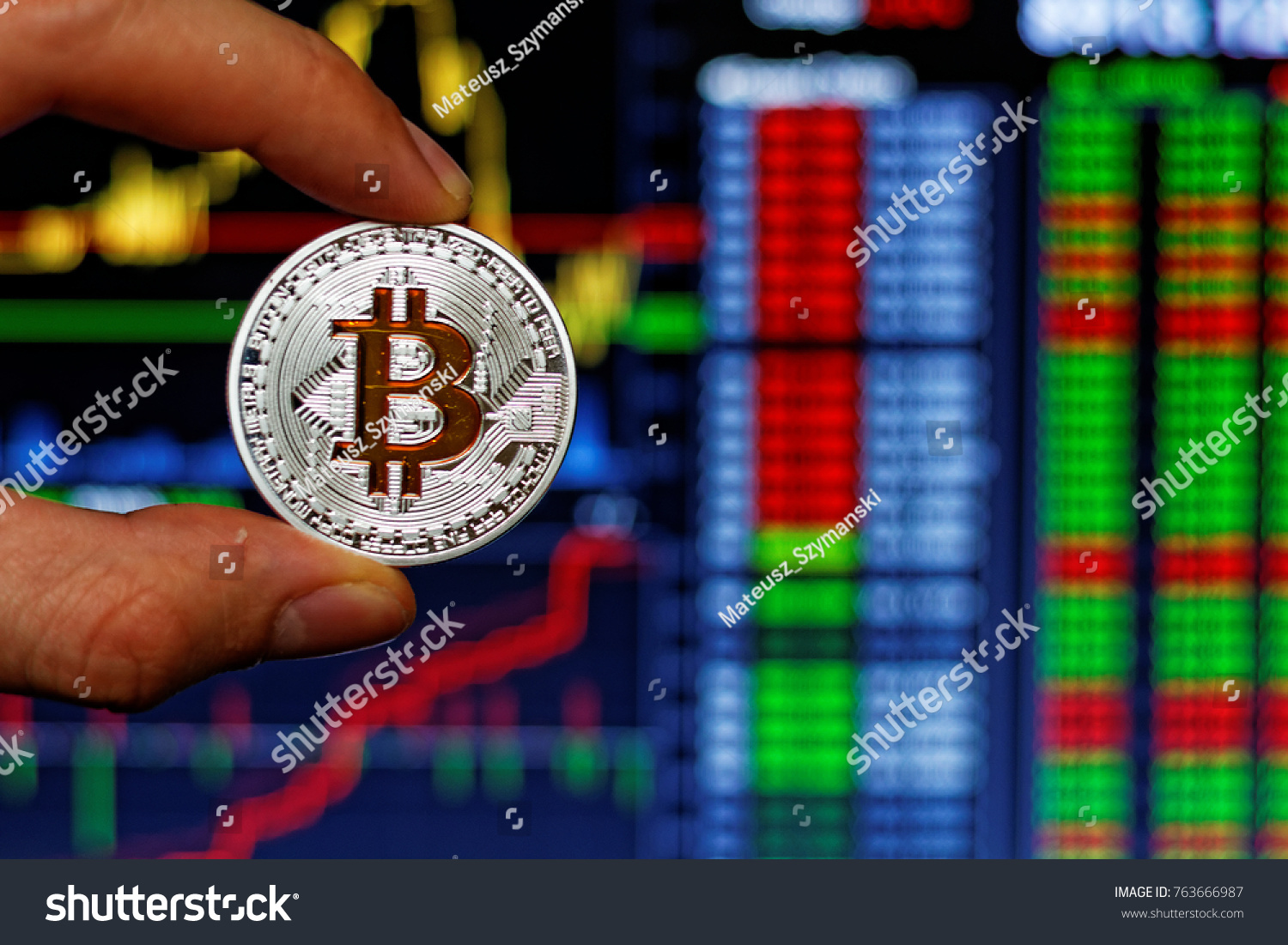 Silver bitcoin gold btc symbol holding stock photo 763666987 silver bitcoin with gold btc symbol holding by mans hand stock market chart background biocorpaavc Images