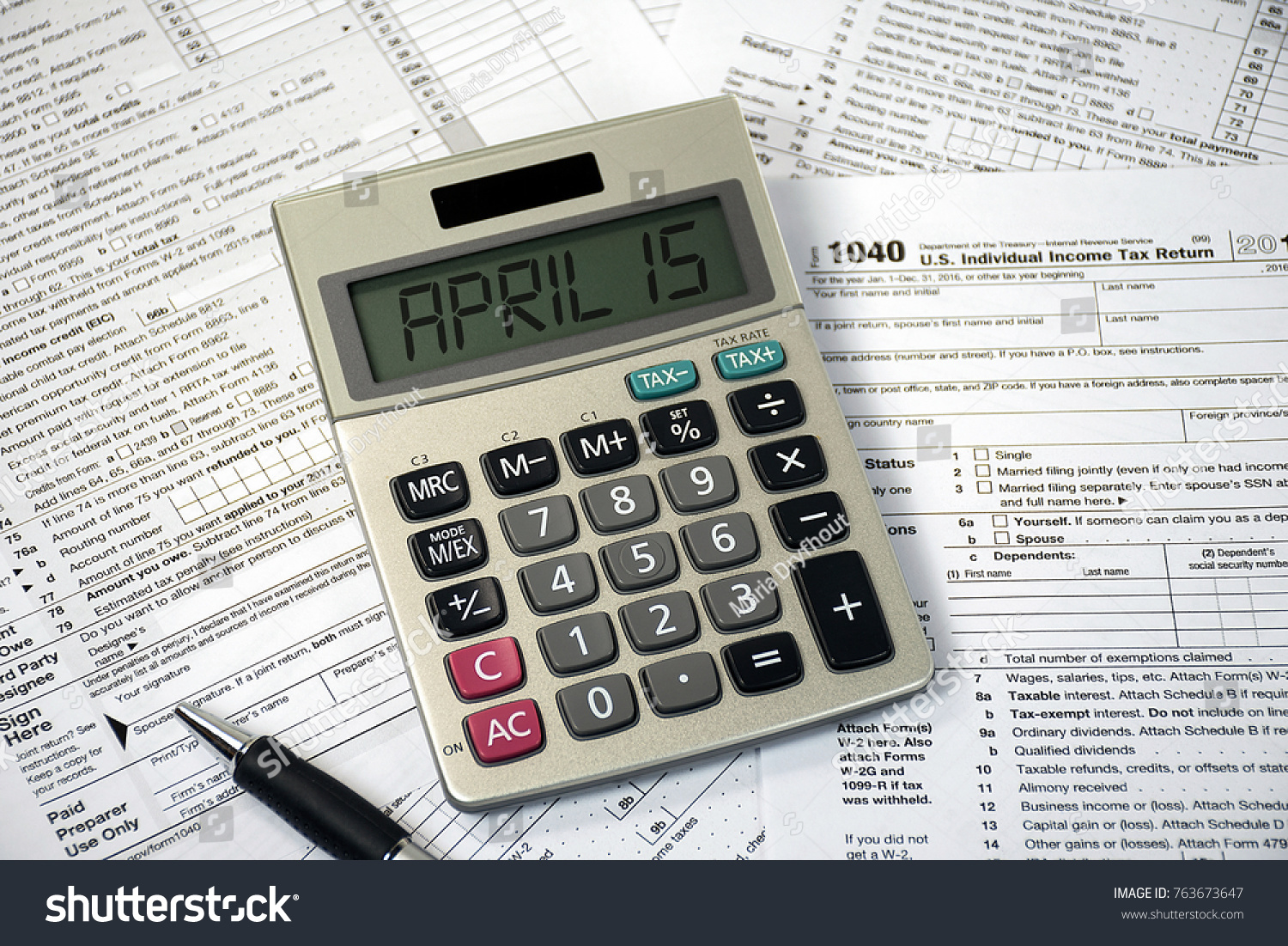 Tax forms with calculator, eyeglasses, pen and sticky note stock.