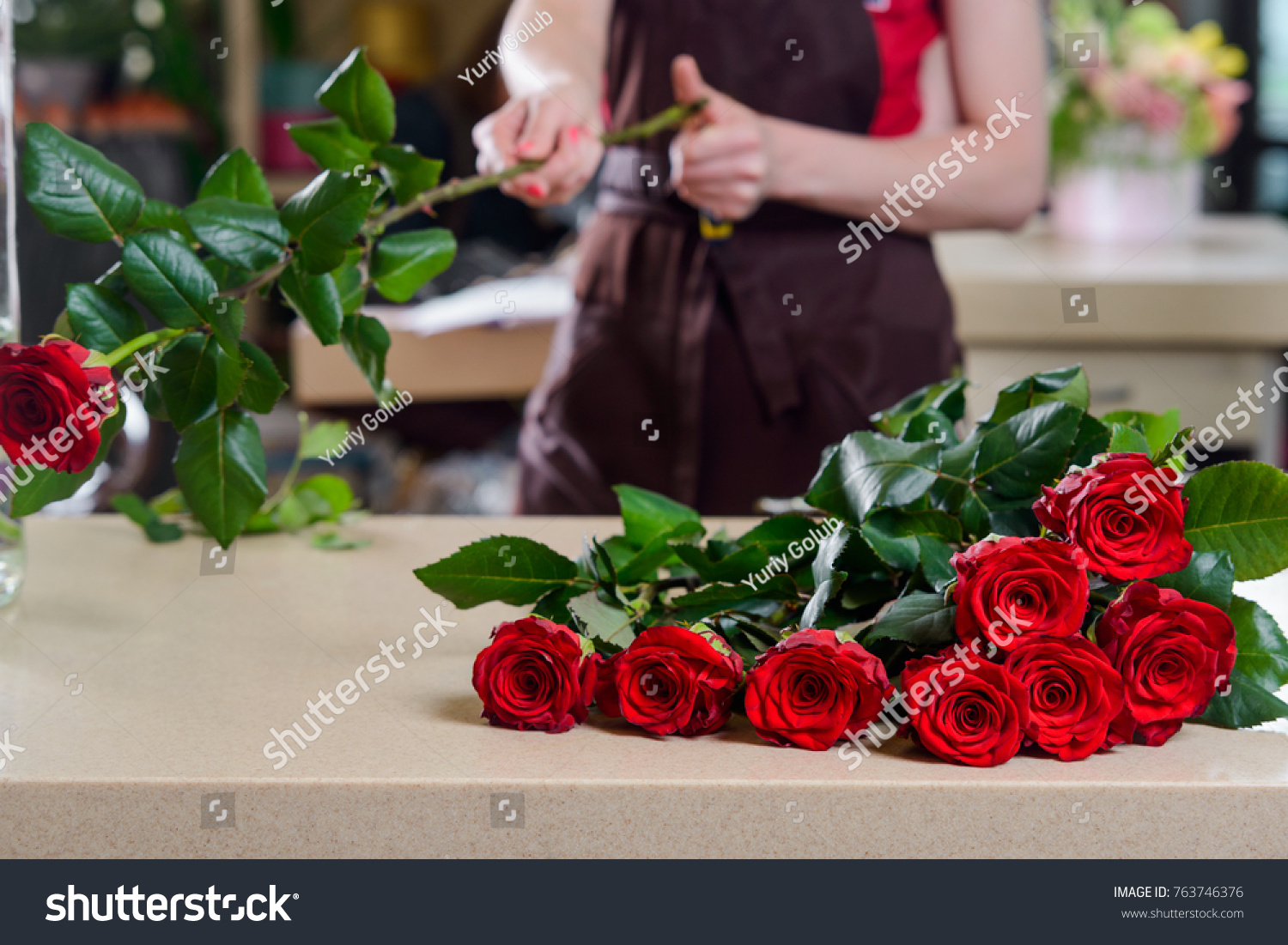 Florist making bouquet red roses woman stock photo edit now florist making a bouquet of red roses woman giving a cut to stems and collecting izmirmasajfo