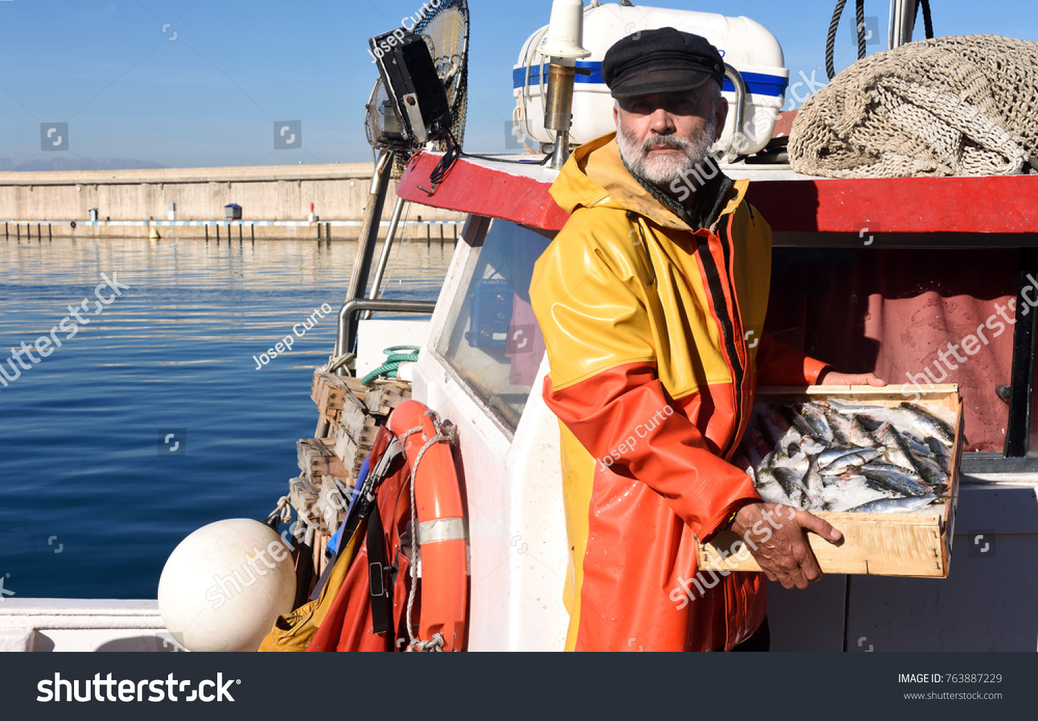 fisherman with a fish box inside a fishing boat #763887229