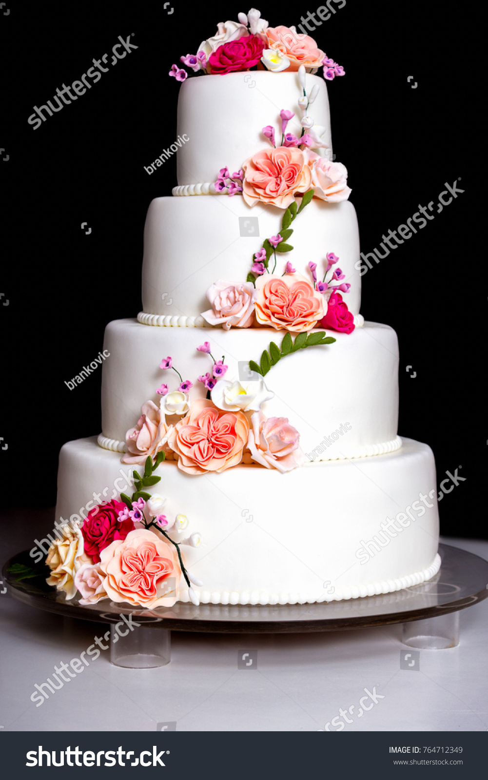 White Wedding Cake With Flowers And Leaves On Black Background