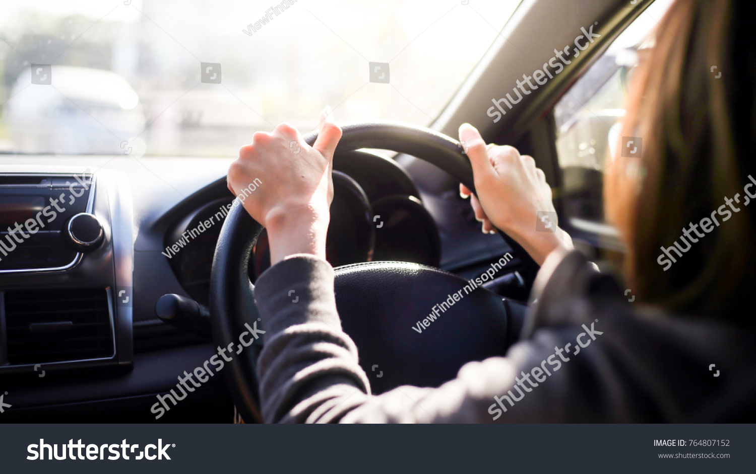 Female hands on the steering wheel of a car while driving. sunset the background, the windshield and road #764807152
