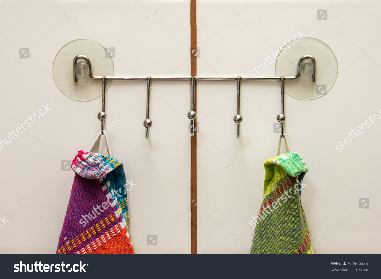 Two Colourful Towels Hanging On A Hooks With Suction Cups In A Kitchen