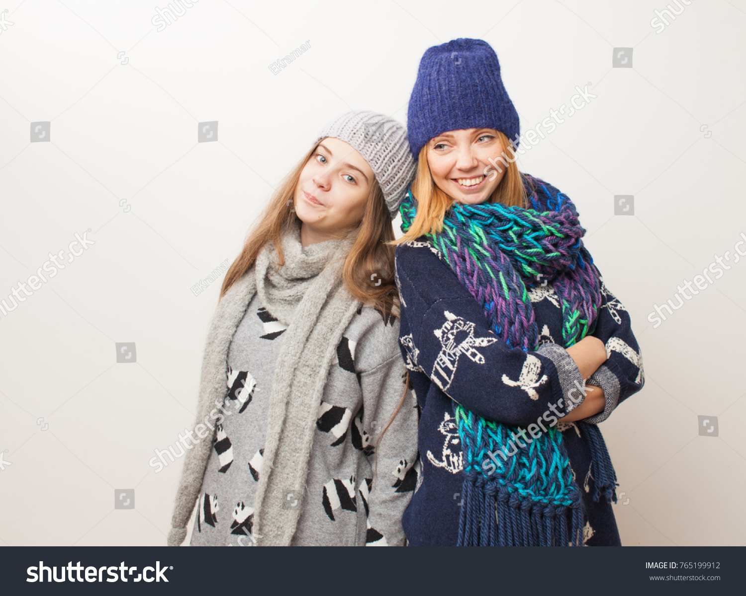 Mom and teen daughter in scarves and hats on a white background. Two girls  enjoy