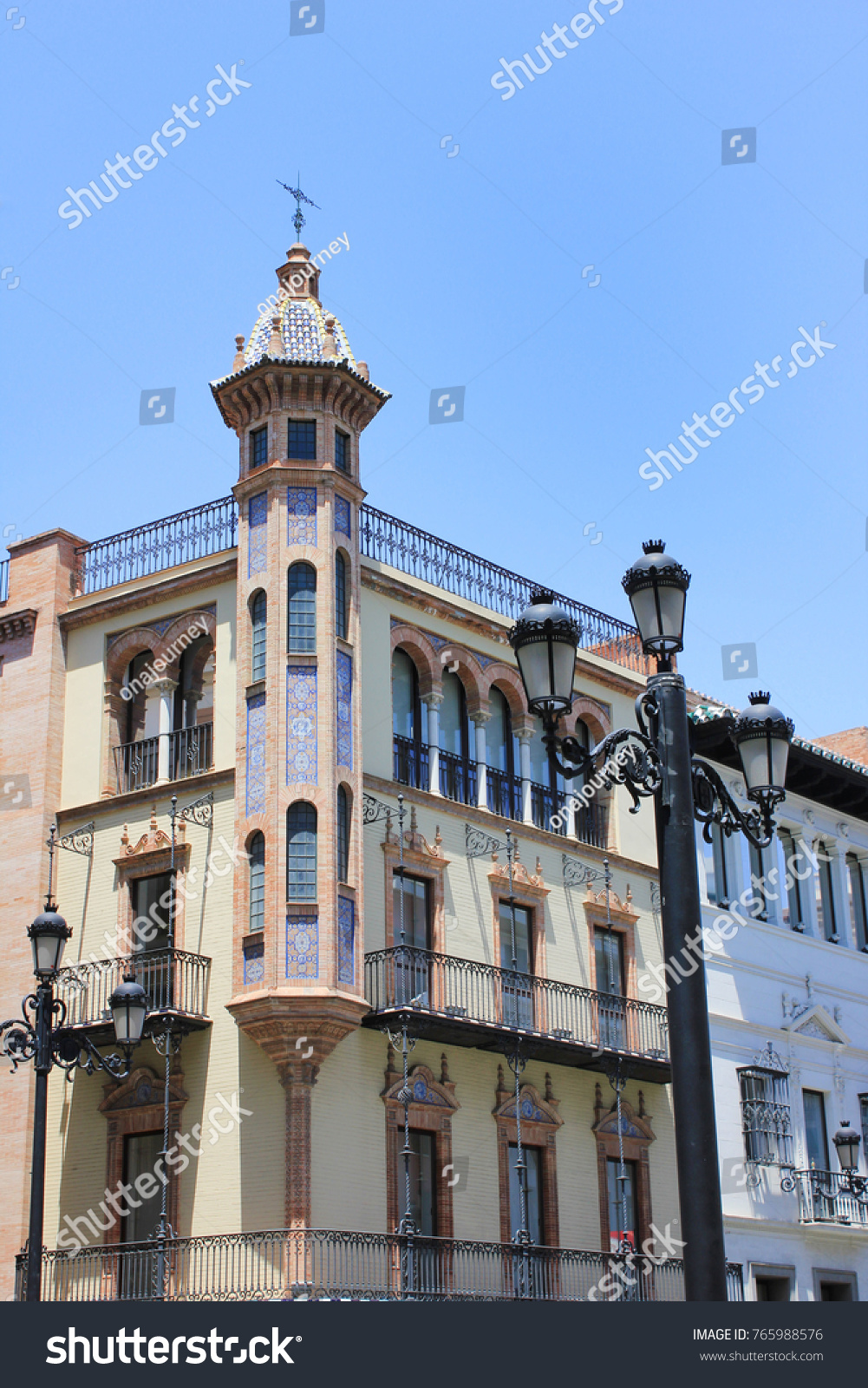 Andalusian Traditional Spanish Architecture Building With Historical Ornamental Windows And Outdoor Lantern In Seville Spain