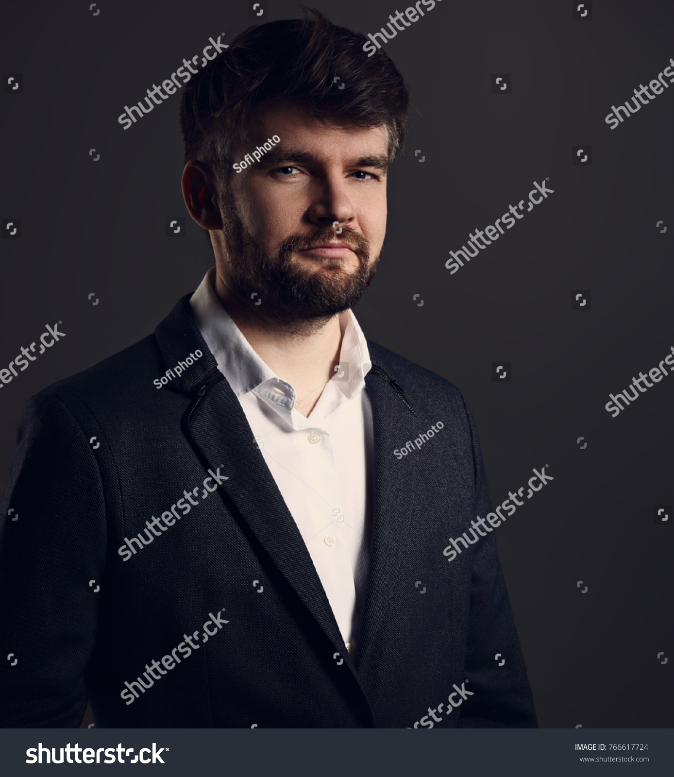 55b1b58e Serious handsome beard male posing in fashion suit and white style shirt  looking on dark grey shadow background. Closeup portrait - Image
