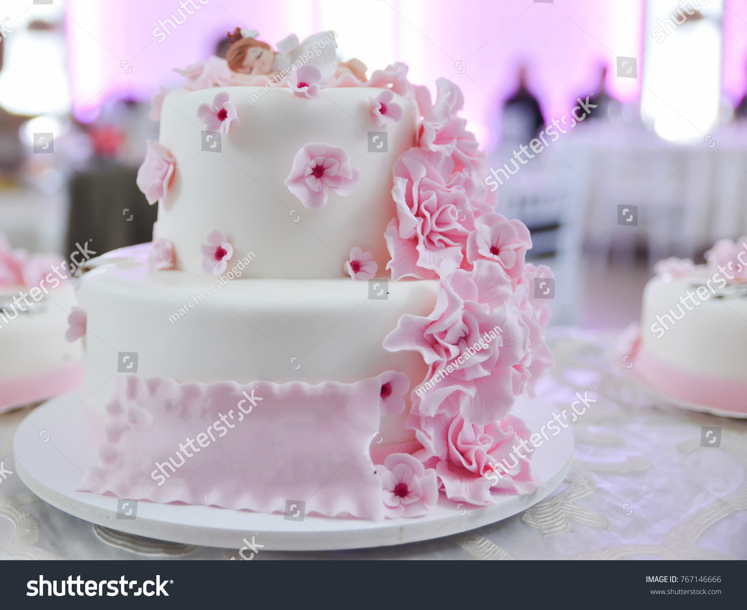 Child Birthday White Cake With Pink Floral Design And Girl Figurine On Top