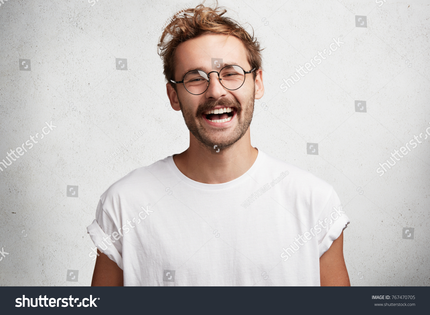 Portrait of glad attractive man with trendy hairdo, beard and mustache, laughs happily at funny story or joke, being in good mood, expresses positive emotions. Satisfied male student finishes work #767470705