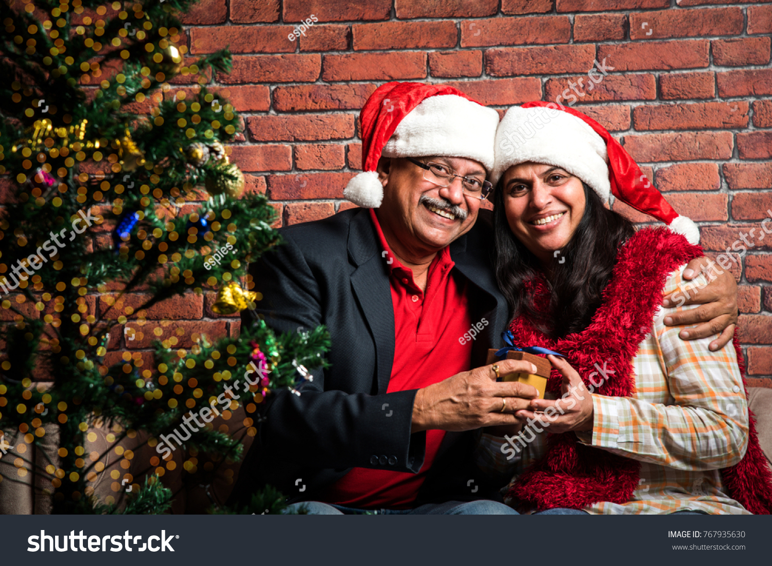 senior indianasion couple celebrating christmas with santa hat and gifts while sitting over sofa