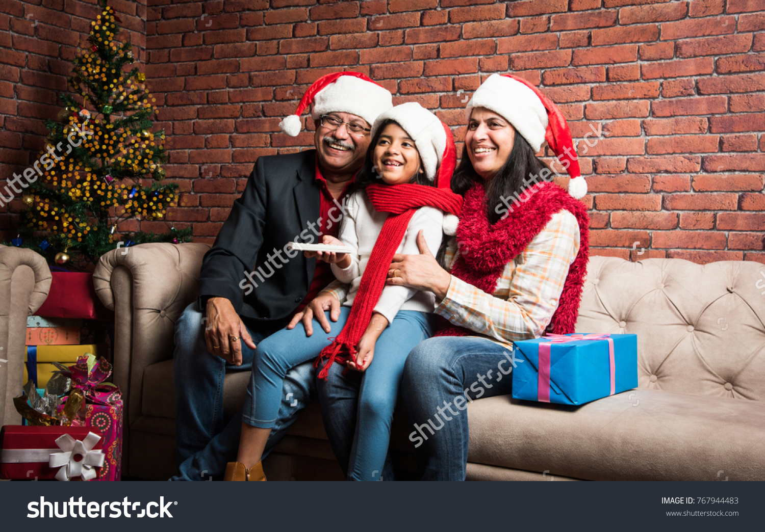 cute little indianasian girl celebrating christmas with grandparents while sitting over sofa and wearing