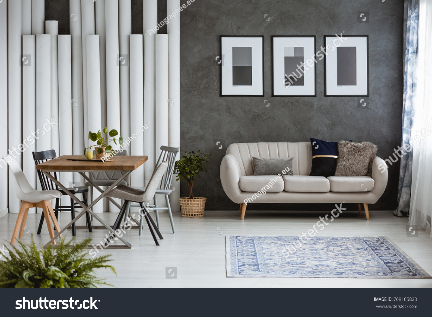 Multifunctional Monochromatic Living Room With Carpet, Dining Table And  Sofa Against Dark Wall With Posters