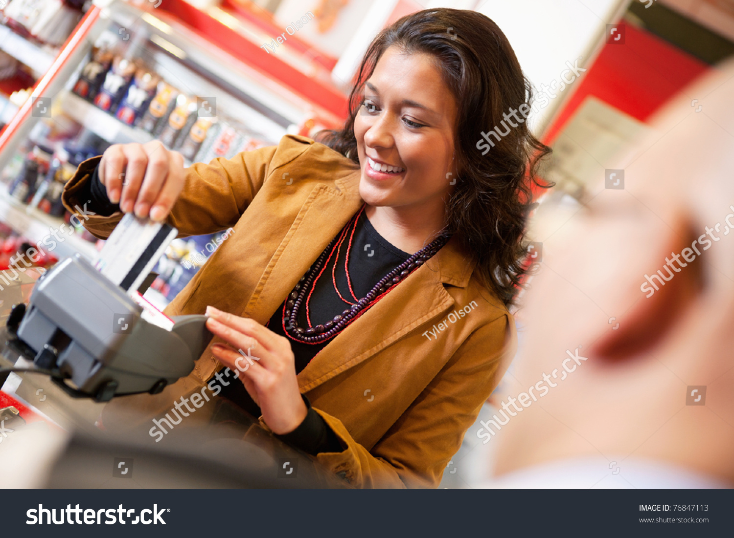 shop assistant smiling while swiping credit stock photo  shop assistant smiling while swiping credit card in supermarket customer in the foreground