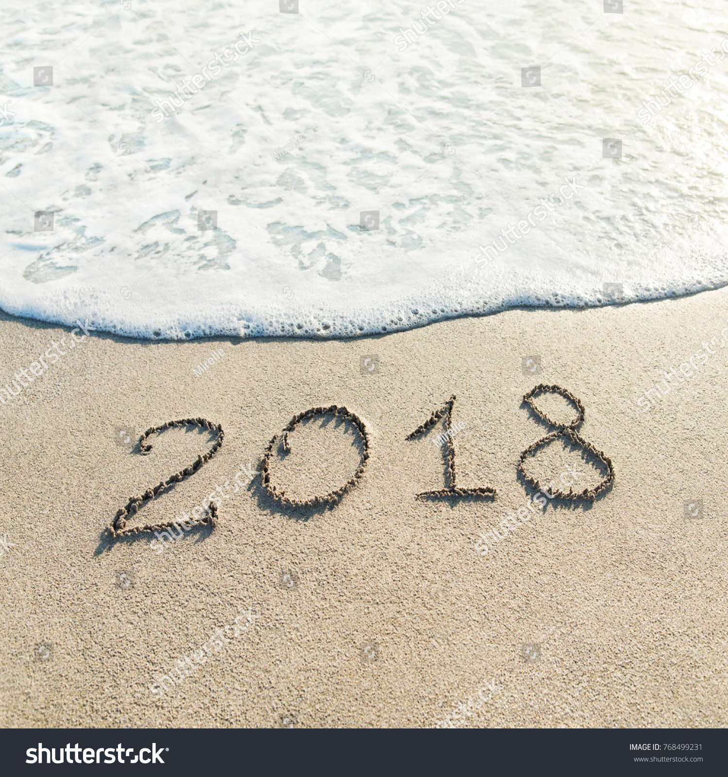 hand lettering happy new year 2018 caption on sand of beach with wave foam winter