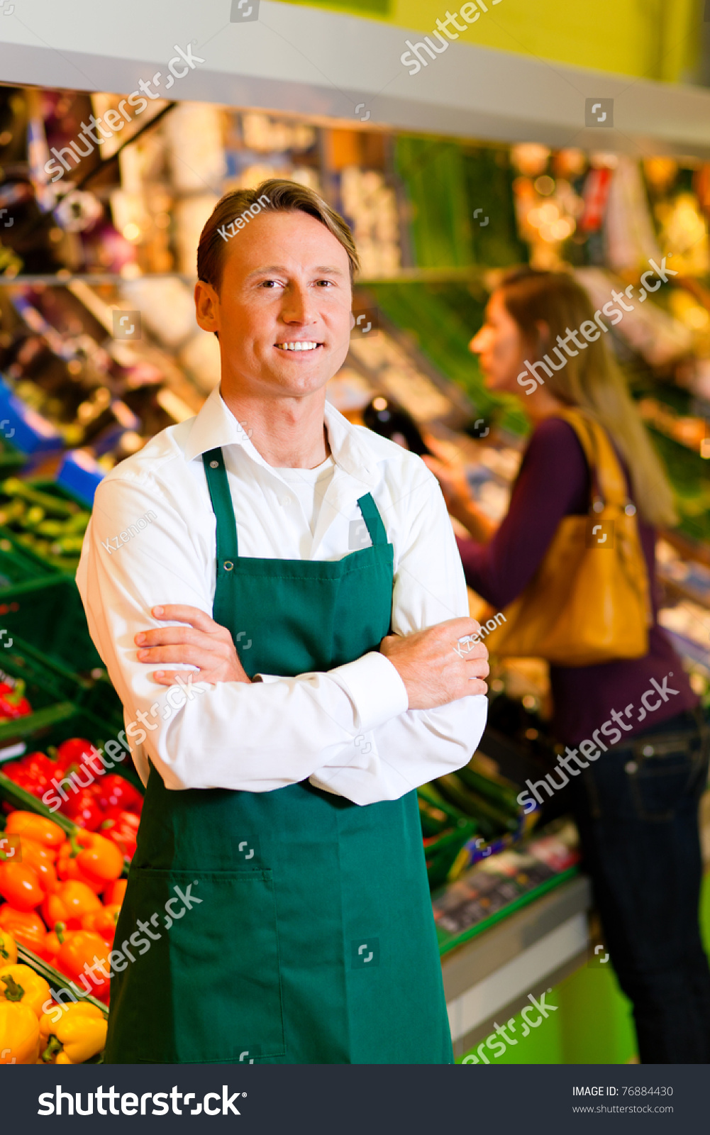 shop assistant in a supermarket at the vegetable shelf in the save to a lightbox