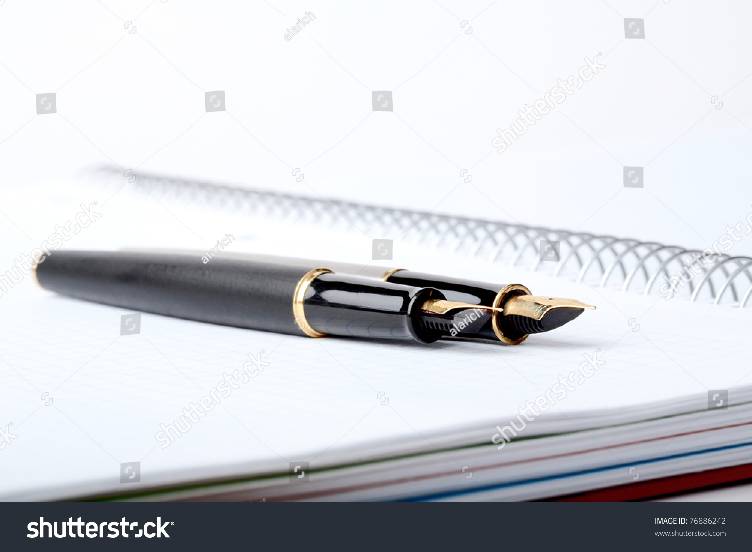 Fountain pens lays on a writing book with spiral stock Writing calligraphy with a fountain pen