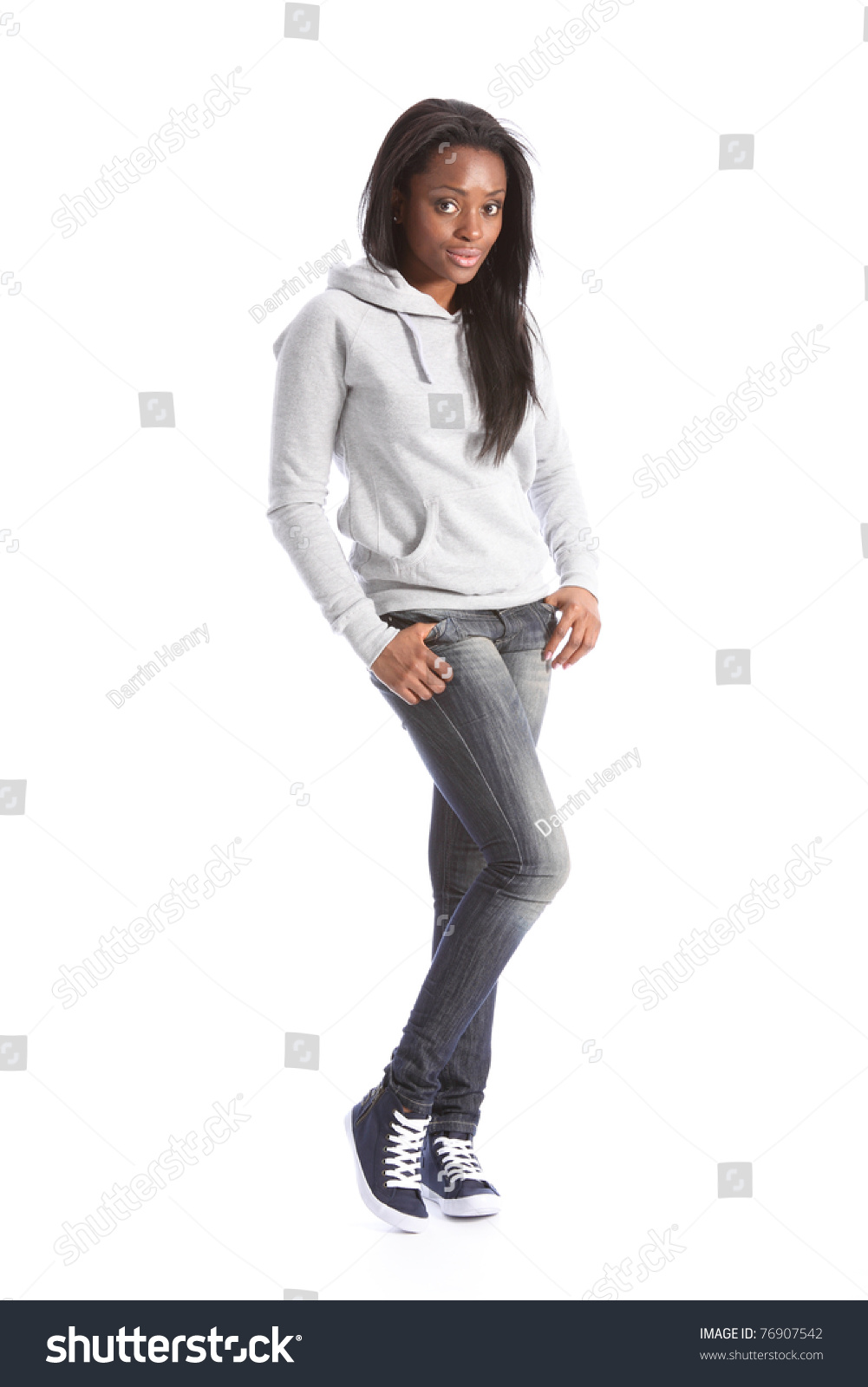 Relaxed standing pose from beautiful young black teenage girl, wearing grey  hoodie sweater and blue