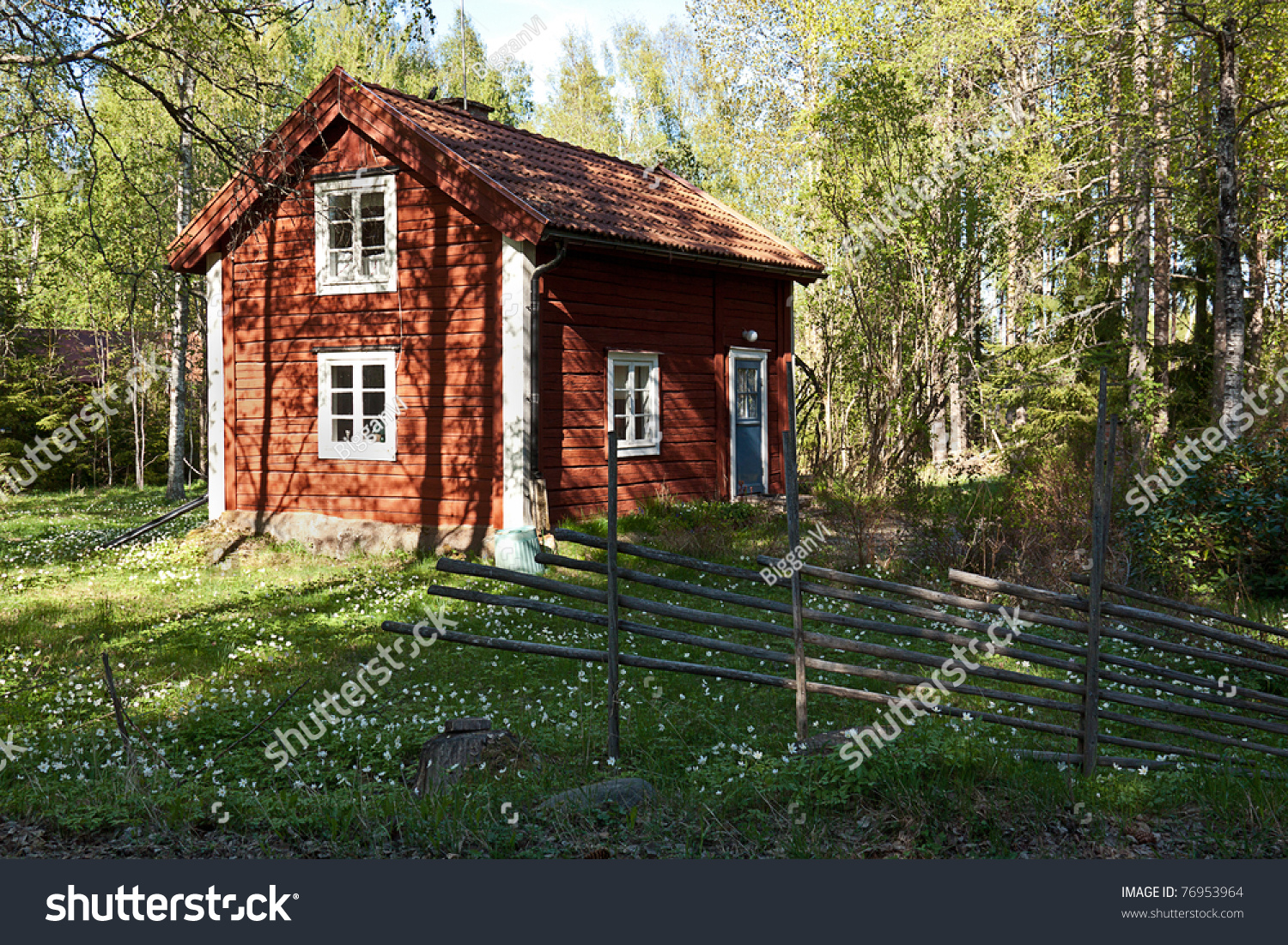 Idyllic swedish house in a forest with old fence typical old wooden painted red