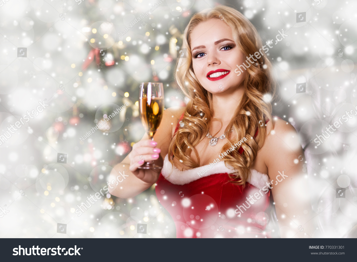 A Beautiful Blonde Woman In A Santa Claus Red Dress Is Surprised Shocked And Ecstatic