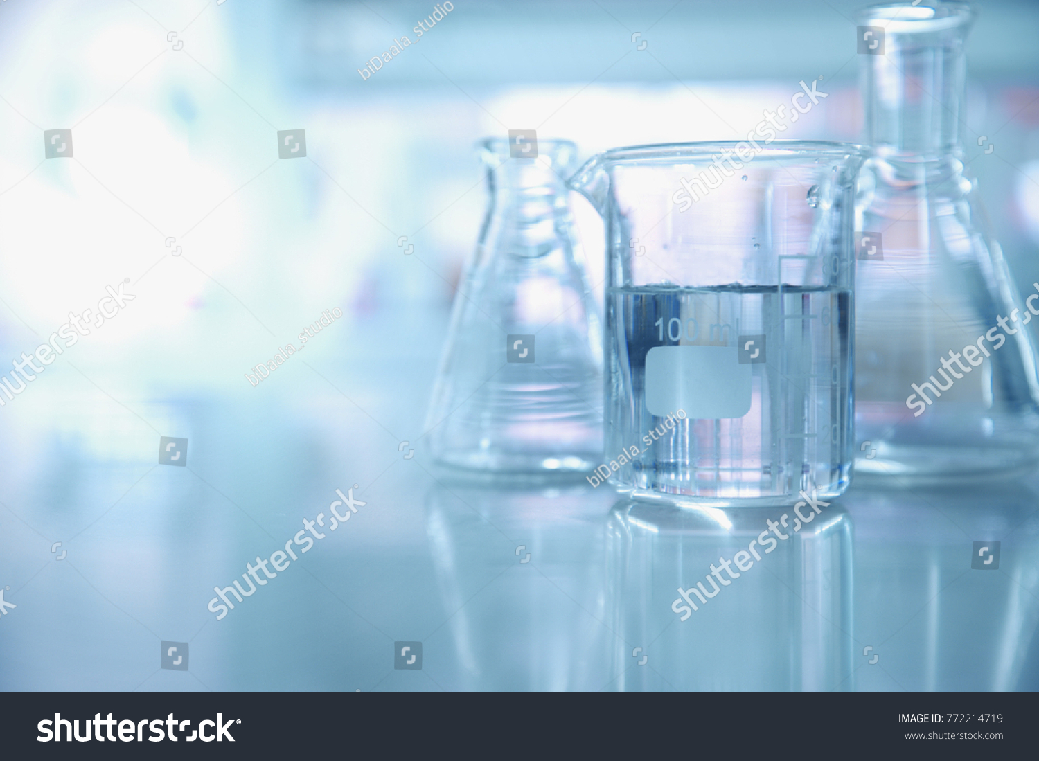 experiment water in beaker and flask in blue chemistry science laboratory background #772214719