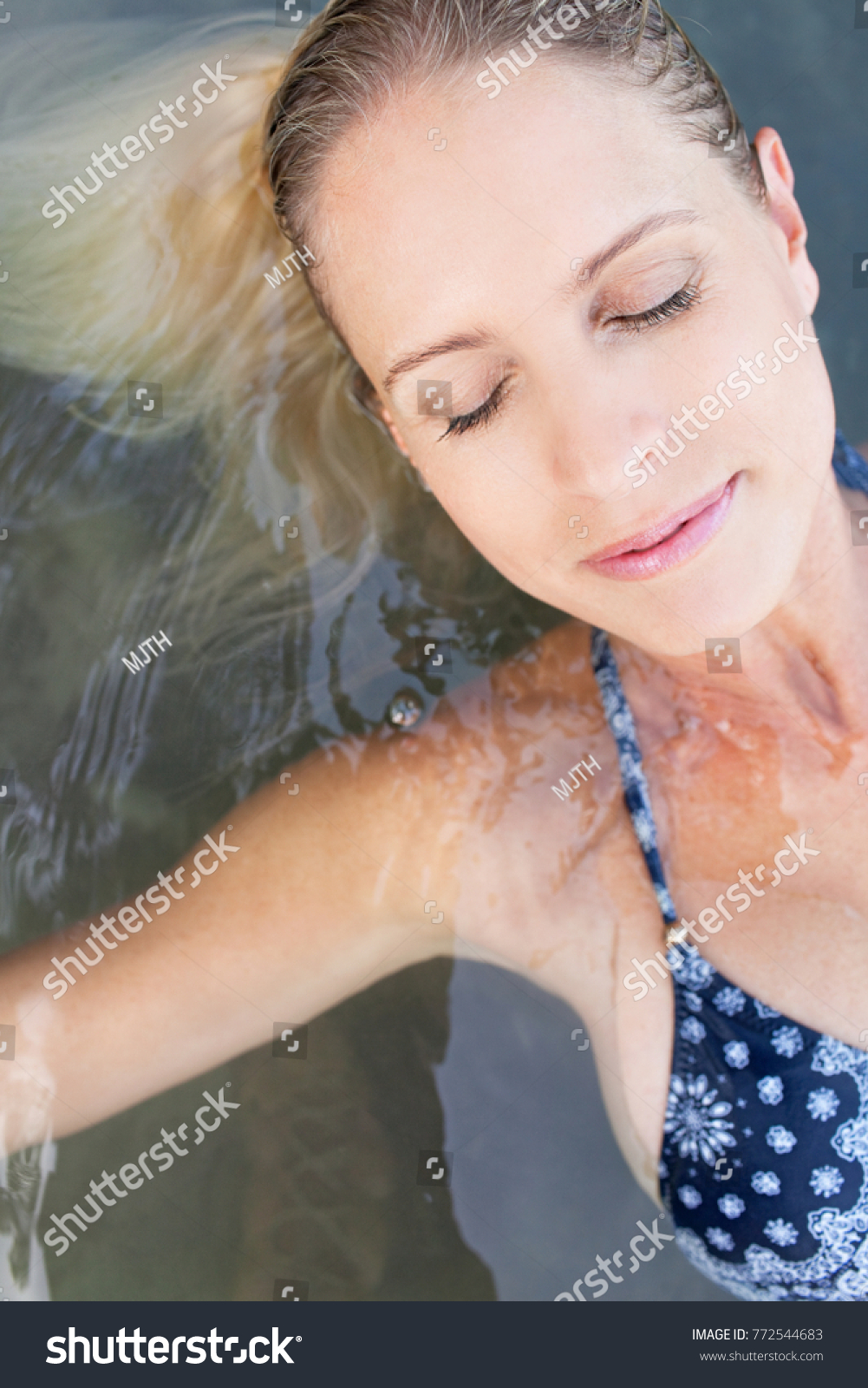 portrait beautiful mature blond woman floating stock photo (royalty