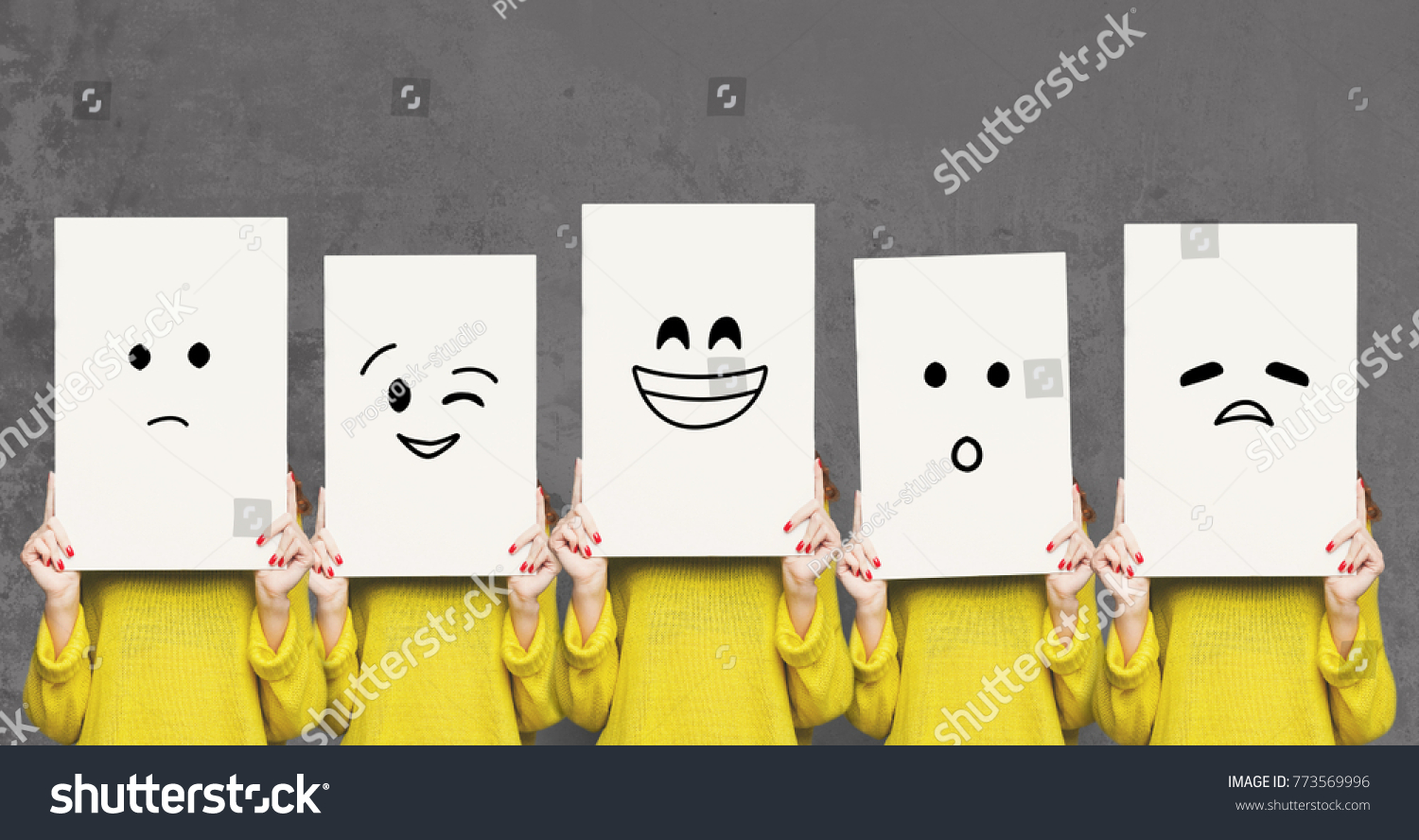 Emotions set. Girl hiding face behind signboard with drawn smileys. Collage of indifferent, winking, happy, surprised, and sad emoticons. #773569996