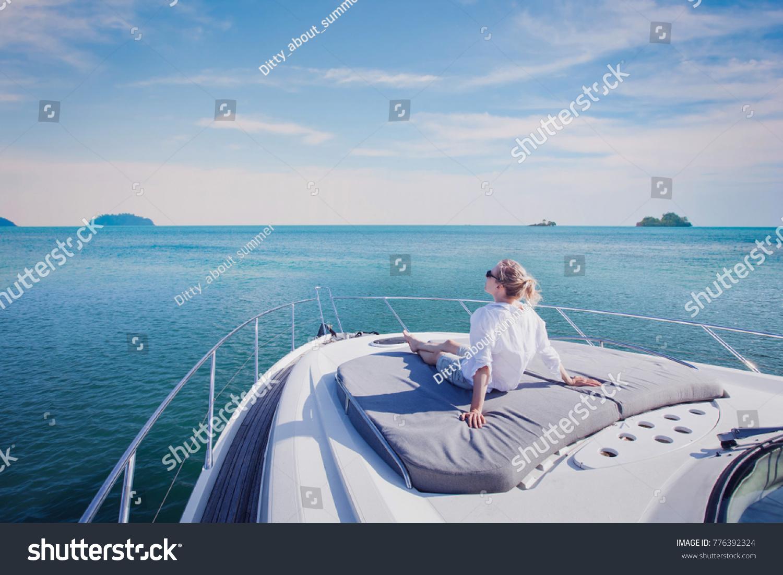 beautiful woman enjoying luxurious yacht cruise, sea travel by luxury boat #776392324