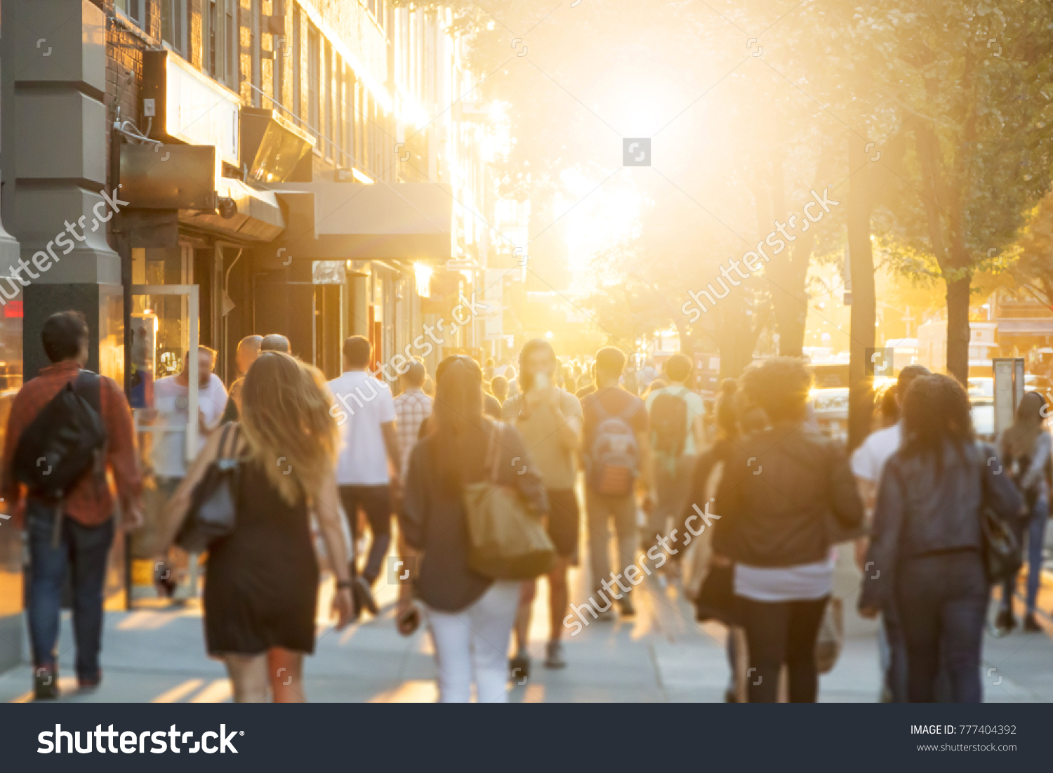 Crowd of anonymous men and women walking down an urban sidewalk with bright glowing sunlight in the background on a busy street in downtown Manhattan, New York City  #777404392